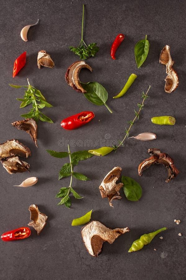 Красные и зеленые зябкие перец, травы и специи на сером backgroun стоковая фотография
