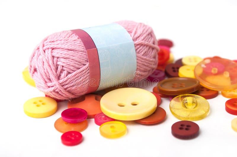 красные и оранжевые кнопки и розовый шарик шерстей на белом ба стоковые изображения
