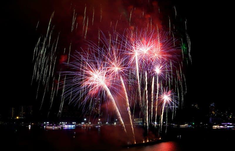 Красные и пурпурные фейерверки брызгая в ночном небе стоковое фото rf