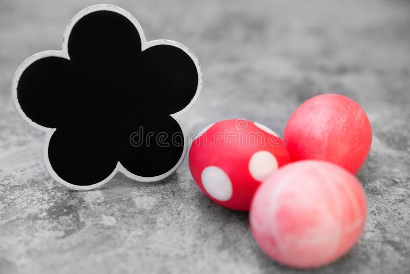 Красные и розовые пасхальные яйца на серой предпосылке, цветут форменный шифер стоковое изображение rf
