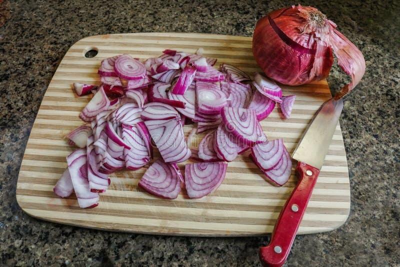 Красные луки отрезанные на деревянной разделочной доске с красным обращанным ножом и всем луком на мраморном countertop стоковое фото