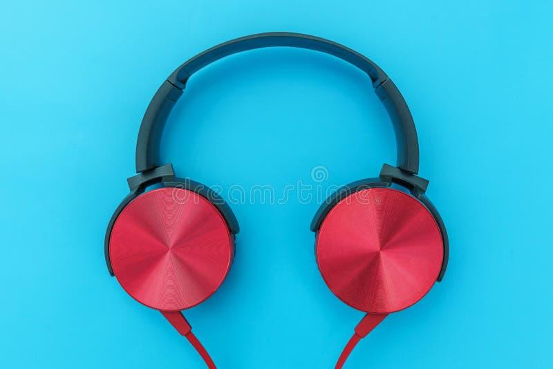 Красные наушники с кабелем изолированным на голубой пастельной красочной предпосылке стоковое изображение