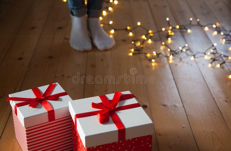 красные ноги подарочных коробок и света рождества на деревянном поле стоковое фото