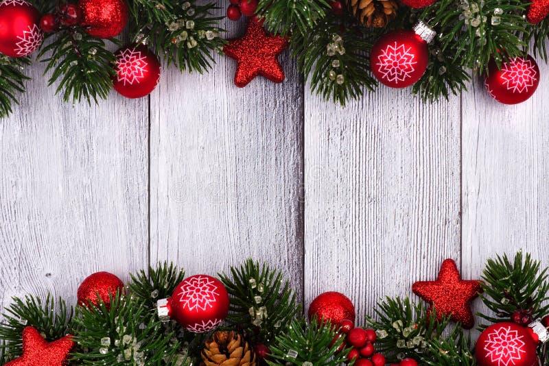 Красные орнаменты и ветви рождества удваивают границу на белой древесине стоковое фото rf