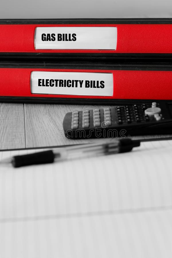 Красные папки с газом и электричеством представляют счет написанный на ярлыке на столе стоковое фото rf