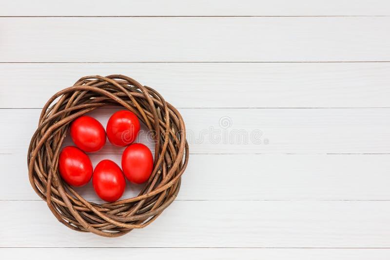 Красные пасхальные яйца в гнезде стоковые изображения