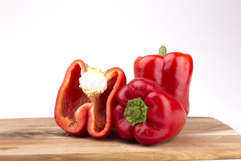 Красные перцы при доска изолированная на белой предпосылке стоковые изображения