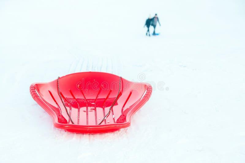 Красные пластиковые сани, розвальни, скелетон на белом снежном outdoors предпосылки Игра и деятельность при зимы для детей стоковое изображение