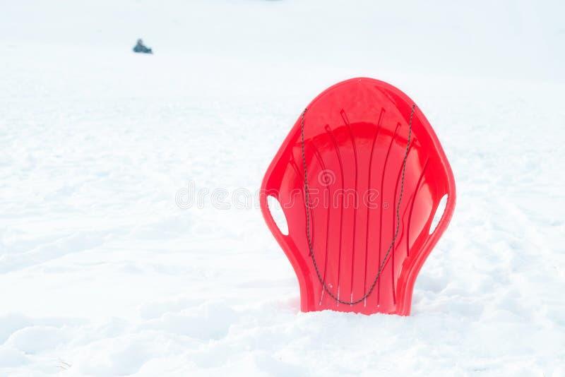 Красные пластиковые сани, розвальни, скелетон на белом снежном outdoors предпосылки Игра и деятельность при зимы для детей стоковые изображения rf