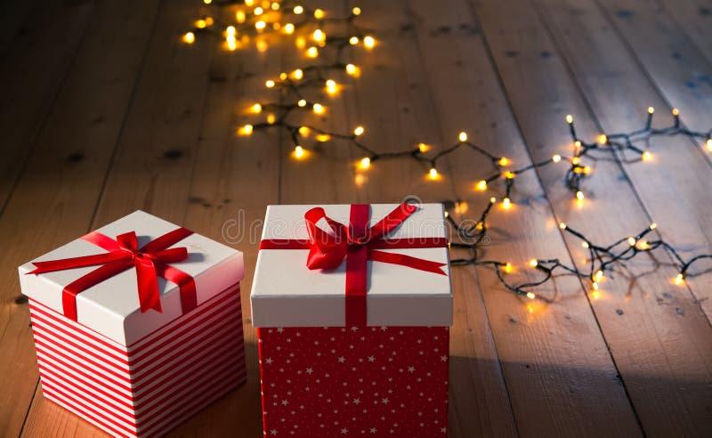красные подарочные коробки и света рождества на деревянном поле стоковые изображения rf