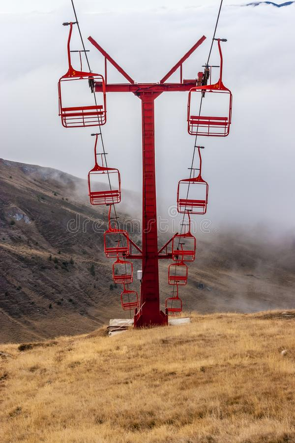 Красные подвесные подъемники в последней осени Пики и облака гор на предпосылке стоковые изображения rf