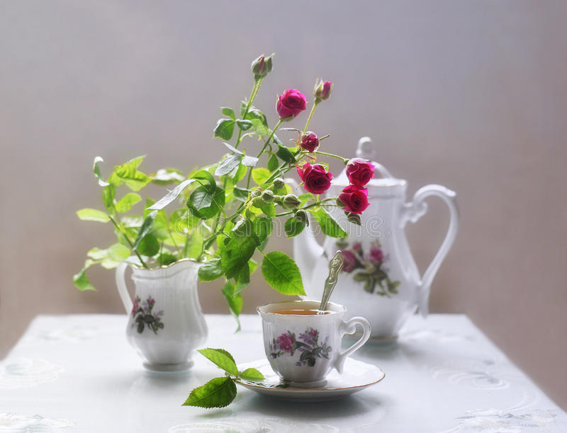 Красные розы и чашка кофе стоковые фото