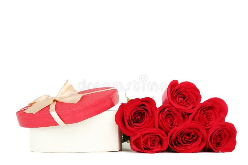 Красные розы с подарочной коробкой сердца форменной стоковое изображение