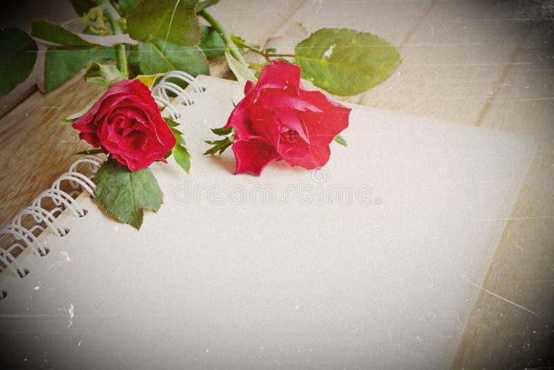 Красные розы цветут и раскрывают тетрадь для текста на деревянной предпосылке стоковые фотографии rf