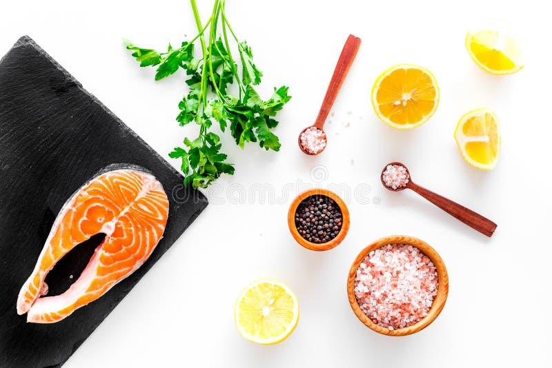 Красные рыбы с специями Salmon стейк на разделочной доске около соли моря, перца, кусков лимона, растительности на белой предпосы стоковые изображения rf