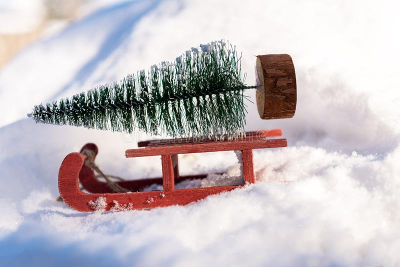 Красные сани нося малую рождественскую елку стоковое фото rf