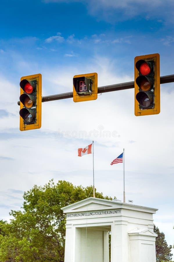 Красные светофоры над флагами Канады и США поверх памятника свода мира стоковое фото