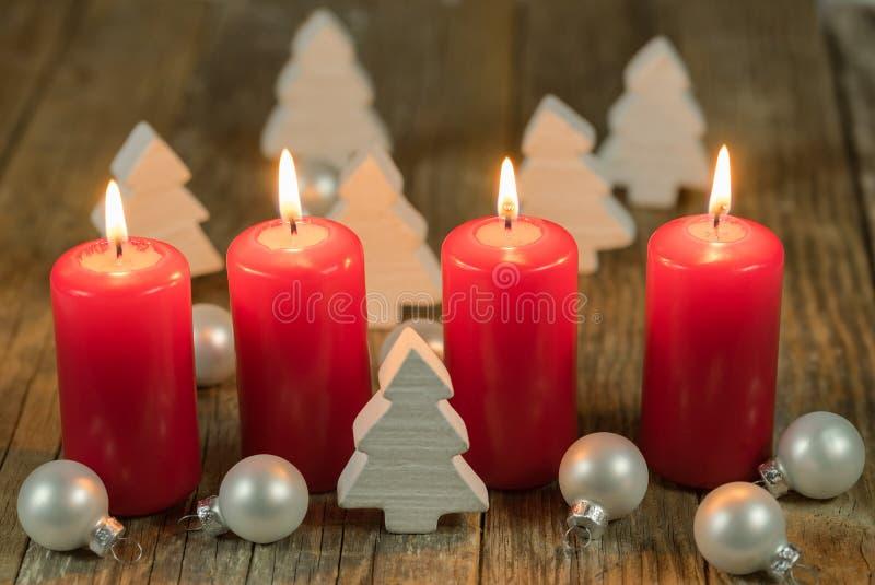 Красные свечи пришествия с 4 горящими пламенами и белыми украшениями стоковые изображения rf