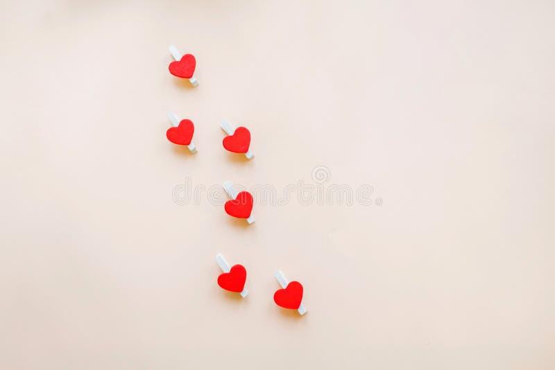 Красные сердца на зажимках для белья для прикреплять стикер который говорит я тебя люблю на бежевой предпосылке Счастливый день В стоковые изображения