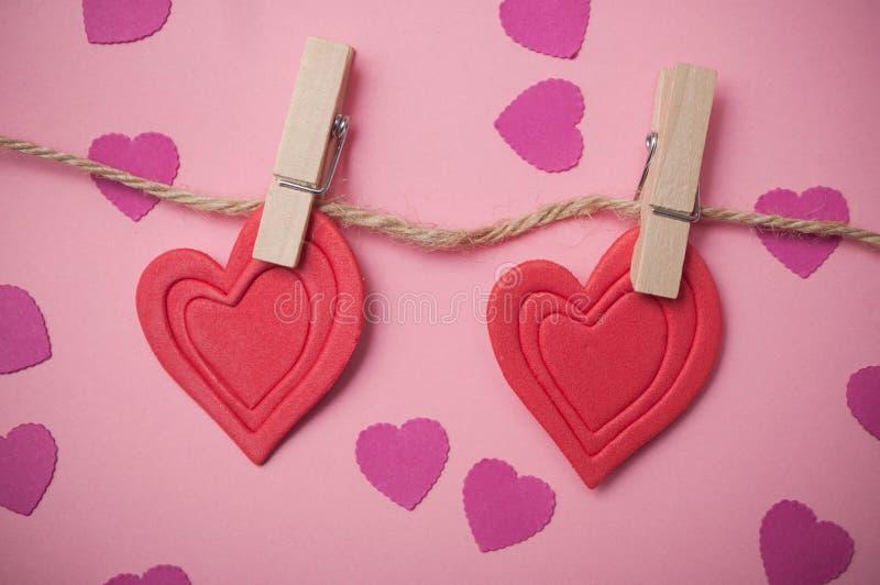 Красные сердца на зажимках для белья на розовой предпосылке - концепции дня Валентайн стоковое фото