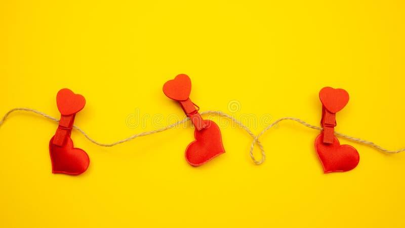 Красные сердца с зажимками для белья на желтой предпосылке, сильной концепции любов стоковое фото