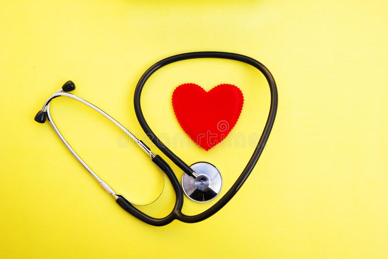 Красные сердце и стетоскоп на желтой предпосылке, здравоохранении сердца и медицинской концепции технологии, селективный фокус, стоковые изображения