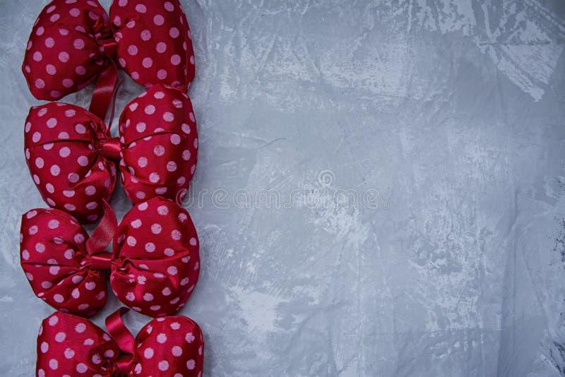 Красные смычки точки польки Игрушка смычка a плюша Светлая предпосылка под бетоном   стоковые фотографии rf