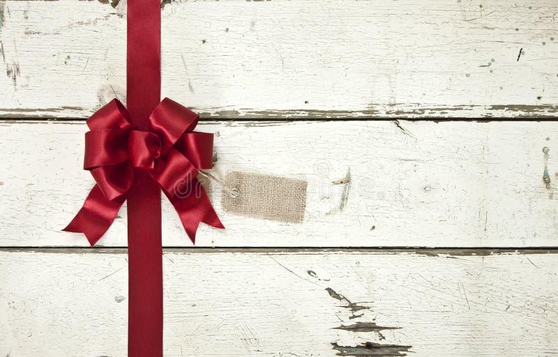 Красные смычок и лента рождества на старом покрашенном белом деревянном backgroun стоковое изображение