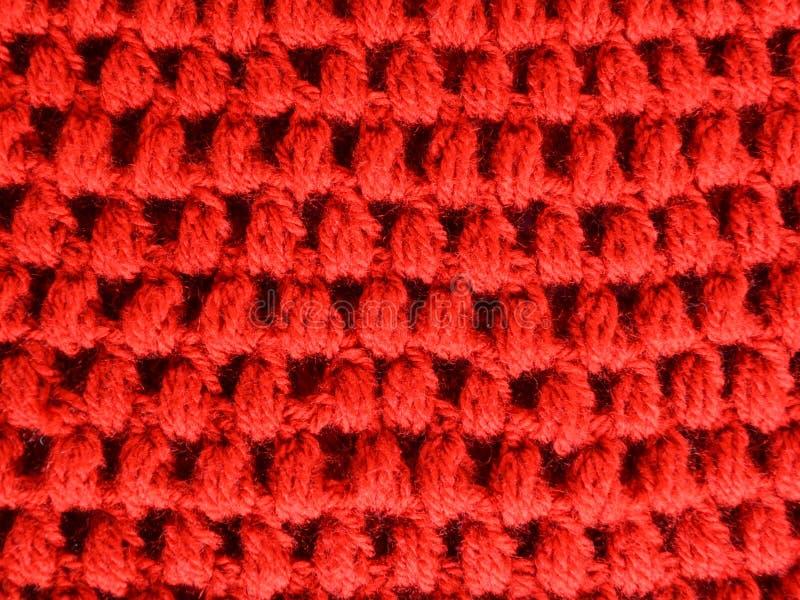 Красные стежки вязания крючком слойки текстуры ткани стоковое фото
