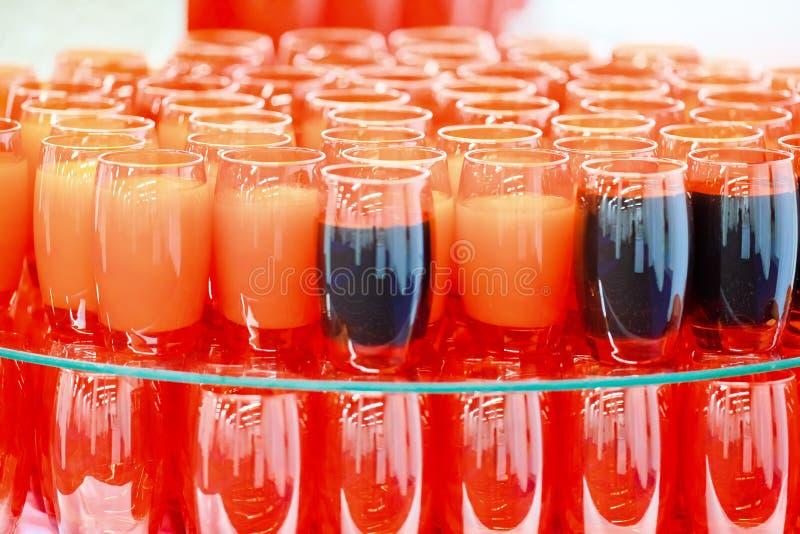 Красные стеклянные чашки полные оранжевого и темного напитка стоковые фотографии rf