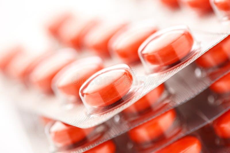 Красные таблетки в пластичной упаковке стоковые изображения