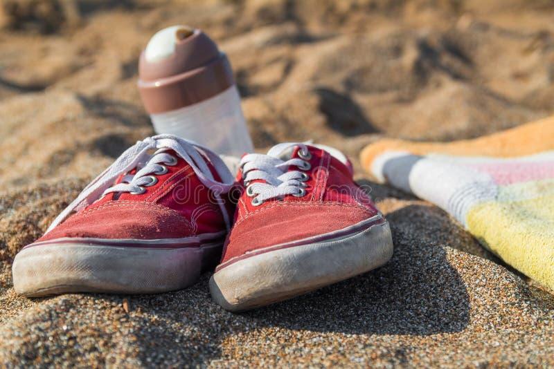 Красные тапки с белыми шнурками на песчаном пляже с шейкером и полотенцем вышли на пляж люди идя для быстрого заплыва в стоковая фотография rf