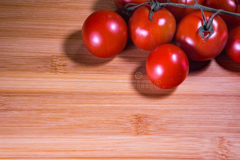 Красные томаты вишни на предпосылке доски Tan стоковое изображение rf