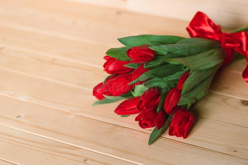 Красные тюльпаны на деревянной предпосылке Красочная карточка на день матерей, день рождения, международный день 8-ое марта ` s ж стоковое изображение