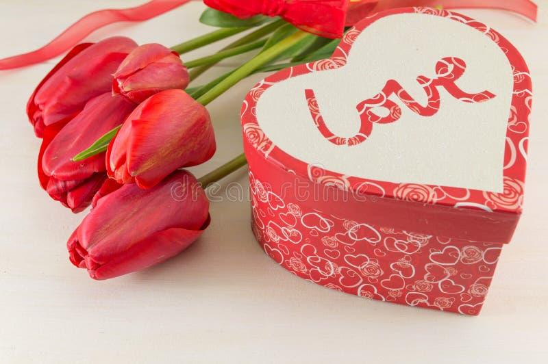 Красные тюльпаны и присутствующая коробка стоковая фотография rf