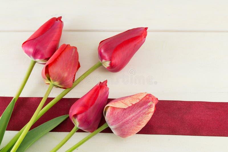 Красные тюльпаны на деревянном столе стоковое фото