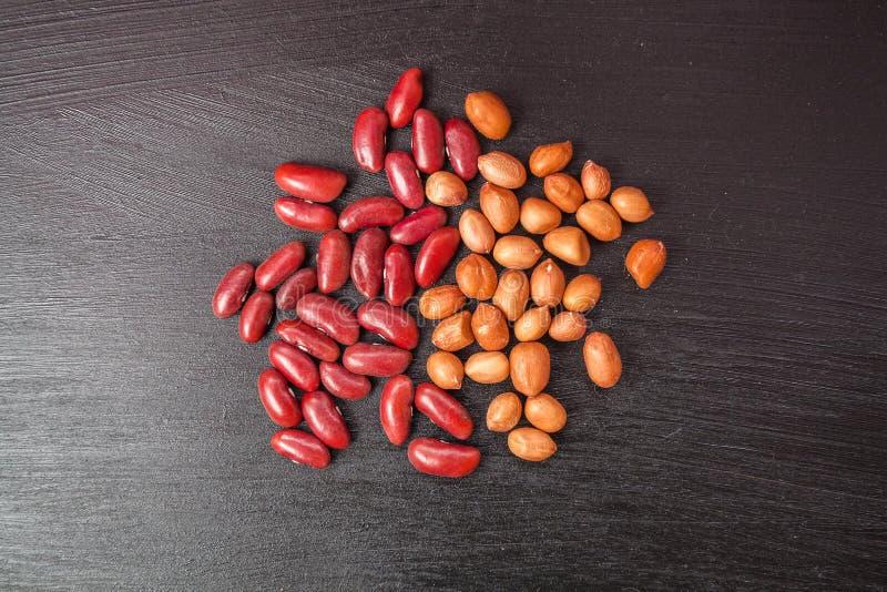 Красные фасоли и арахисы на деревянной предпосылке стоковое изображение rf