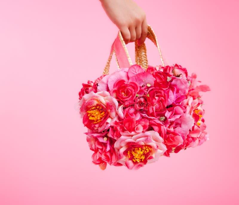 Красные цветки кладут в мешки в руке женщины на розовой предпосылке стоковое изображение