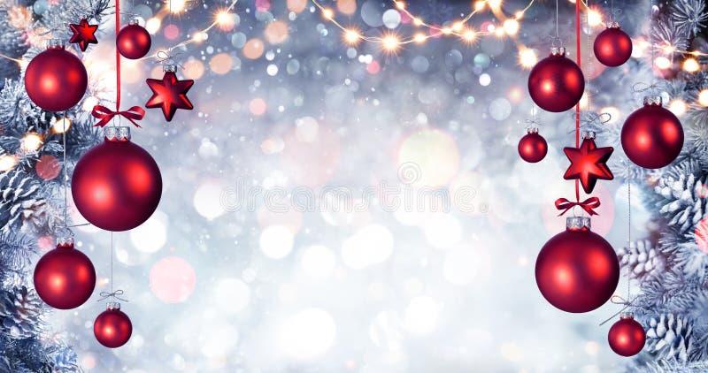 Красные шарики рождества вися с елью Snowy разветвляют стоковая фотография rf