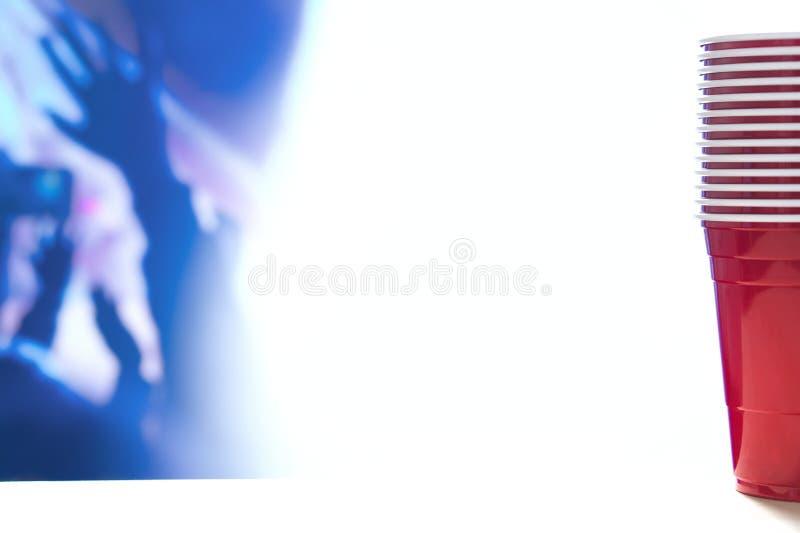 Красные штабелированные чашки партии Шаблон предпосылки партии коллежа тематический Белый фон Контейнеры спирта стоковая фотография