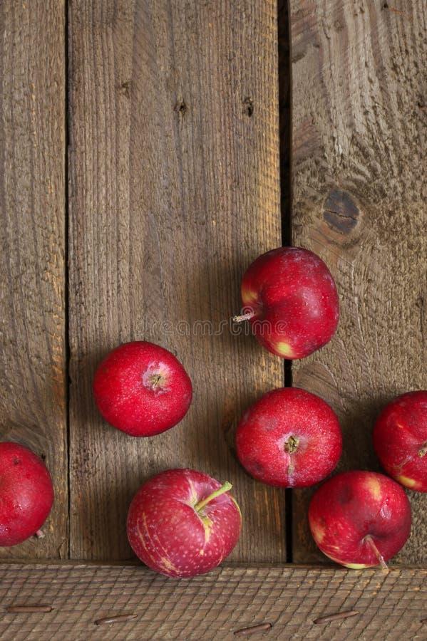 Красные яблоки на деревенской древесине стоковое изображение