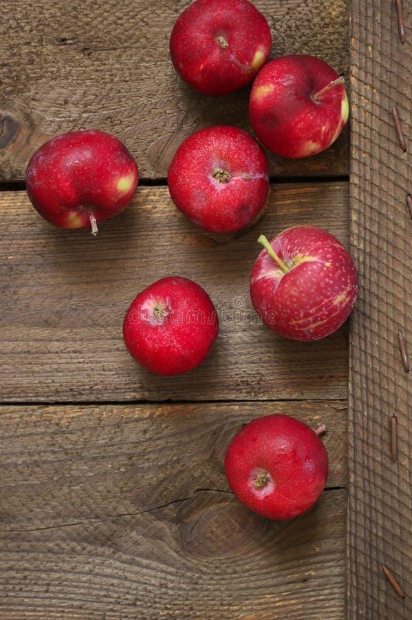 Красные яблоки на деревенской древесине стоковая фотография