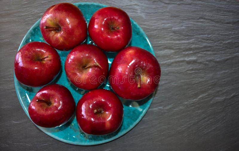 Красные яблоки на плите стоковые изображения rf