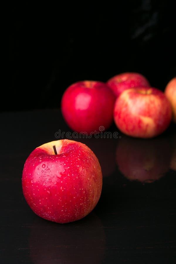 Красные яблоки на черной предпосылке влажно стоковое изображение