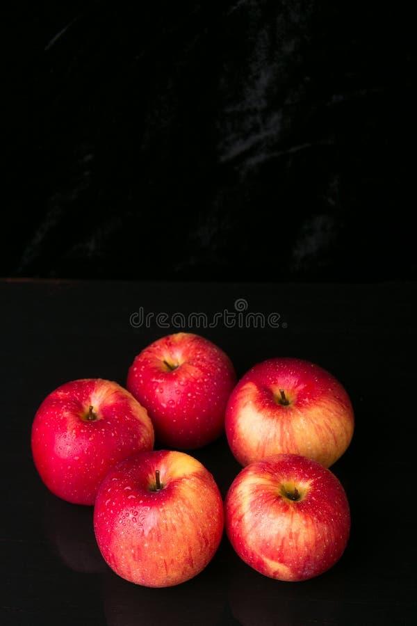 Красные яблоки на черной предпосылке влажно стоковые фотографии rf