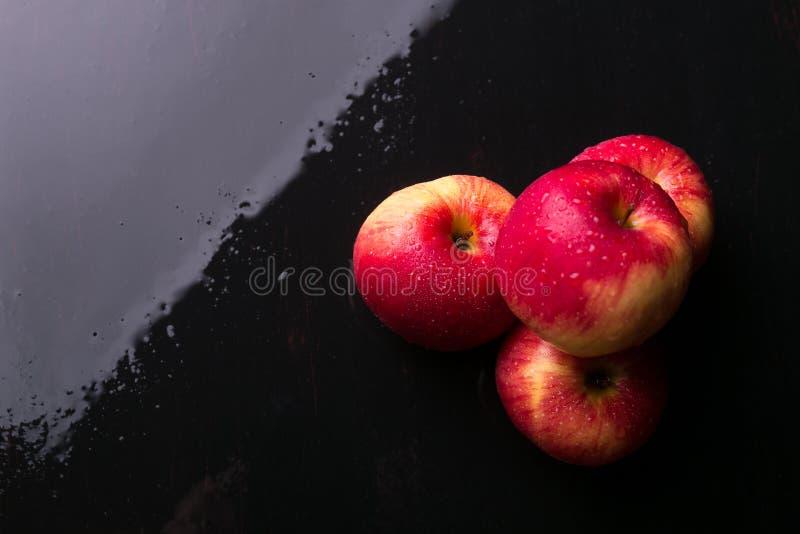 Красные яблоки на черной предпосылке влажно стоковое фото