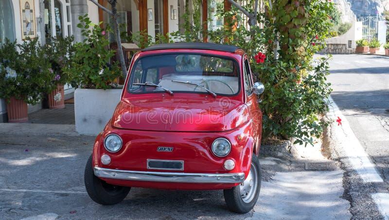 Красный автомобиль классики Фиат Cinquecento 500 припаркованный с улицы на побережье Амальфи, Италии стоковые фотографии rf