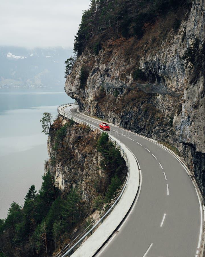 Красный автомобиль на дороге около горных вершин гор швейцарских, Швейцарии стоковое фото rf