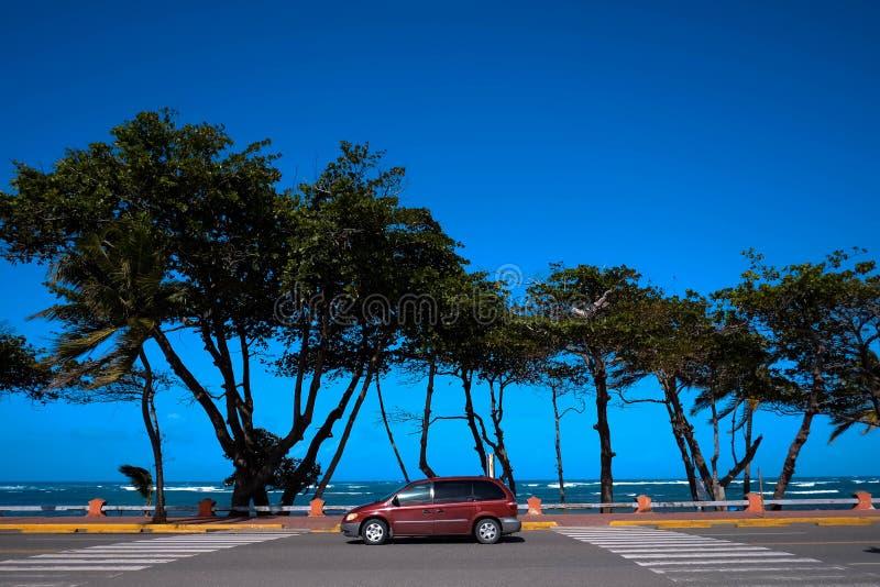 Красный автомобиль припаркованный на тропическом взморье пляжа в горячем ветреном солнечном дне стоковое изображение rf