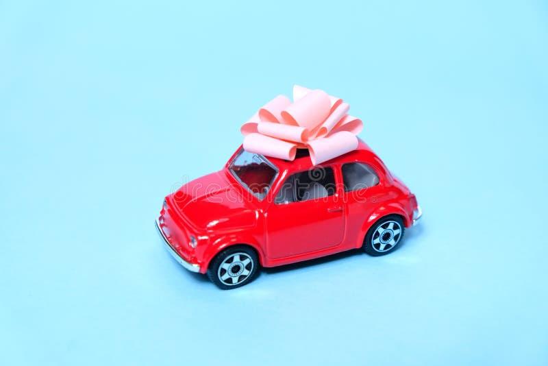 Красный автомобиль связан со смычком подарка Концепция настоящего момента стоковое изображение rf